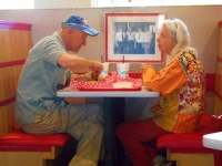 Funky dressed old couple dining out.