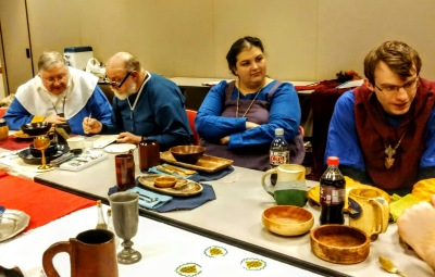 4 medieval attired people sit on one table side waiting to select buffet food.
