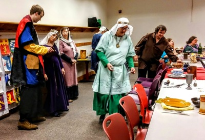 Medieval attired people. A few placing table settings. Others talking before court.