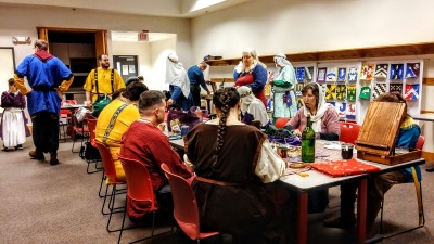 Seated and standing medieval attired people, crafting and talking,