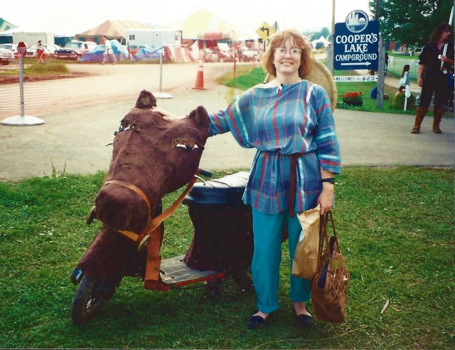 Woman with a scooter. Handlebars covered with a paper-mache horse's head.