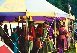Many people in medieval clothing socializing under a huge purple and yellow tent.