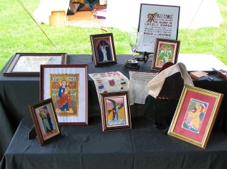 display of multiple hand painted medieval-style pictures, embroidery, and glass