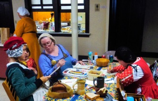 3 women in medieval style clothing sit at a table painting and talking
