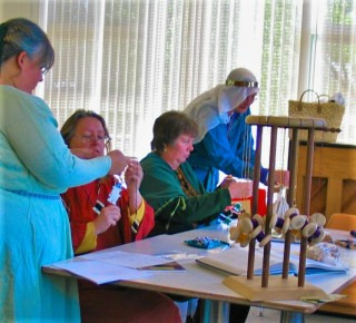 4 medievally dressed women at a table with kumihimo braiding supplies