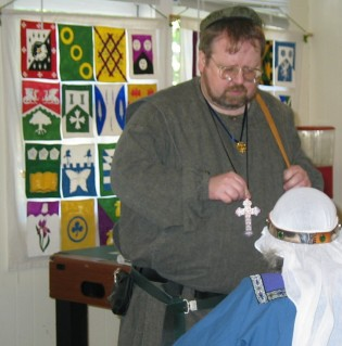 A medievally dressed man teaching in front of many heraldic devices.