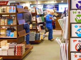 A woman in jeans and  coat is seen looking at a bookstore item viewed from between the stacks of books.