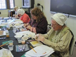 Three Ladies in medieval clothing at a table making paint