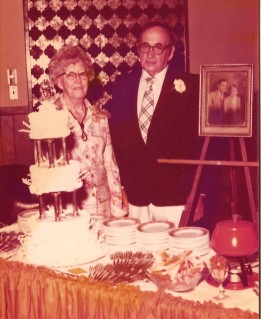 older man and woman stand behind a buffet table on their 50th anniversary