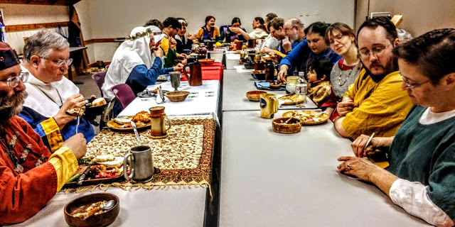 View from the long end of a table with 25 medieval attired people eating.